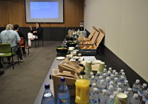 A long table displays boxes of bagels and pastries, bowls of fresh fruit, and different beverages